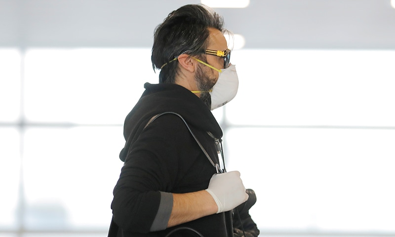 A traveler wears a mask while walking through John F Kennedy International Airport amid coronavirus fears in New York on March 11. — Reuters