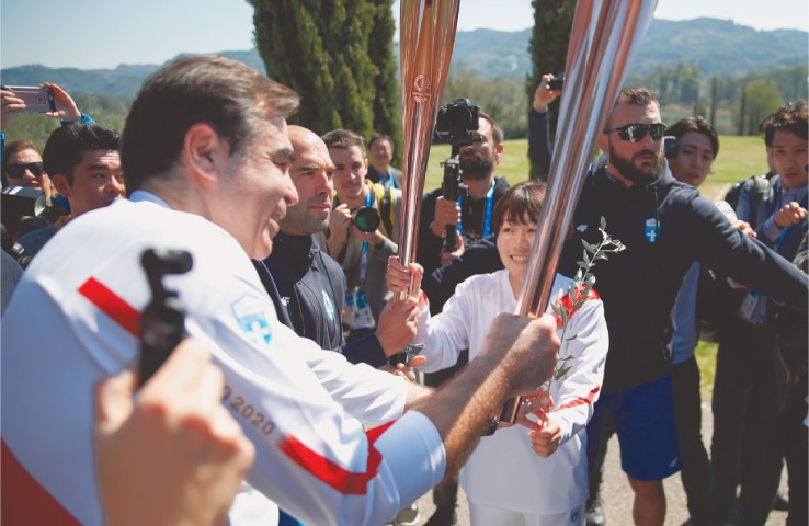 JAPANESE Olympic marathon champion Mizuki Noguch (C) passes the torch of the 2020 Tokyo Olympics to European Commissioner following the flame lighting ceremony at the closed Ancient Olympia site in southern Greece on Thursday.—AP