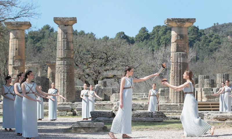 GREEK actress Xanthi Georgiou (C), playing the role of the High Priestess, holds a torch during the flame lighting ceremony at the Ancient Olympia site, birthplace of the ancient Olympics in southern Greece, on Thursday—AP