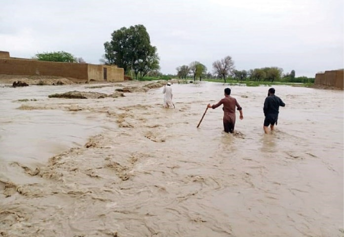 People wade through a rainwater nullah in Daraban Kalan, Dera Ismail Khan, on Thursday. — Dawn