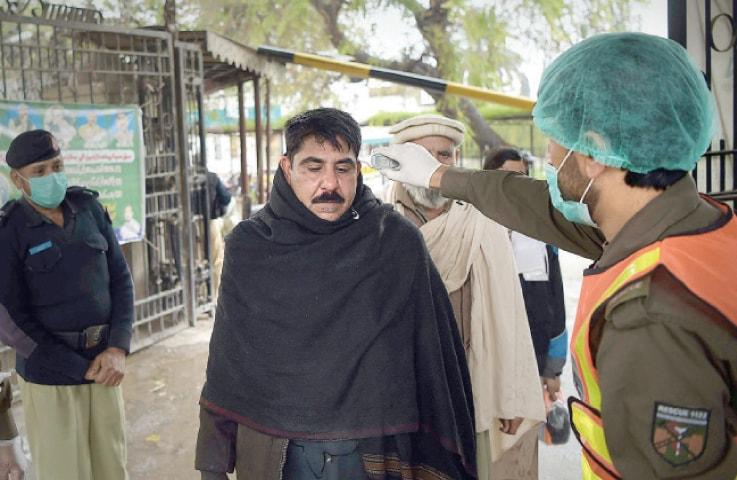 A Rescue 1122 worker scans employees at Civil Secretariat, Peshawar, on Thursday for coronavirus. — White Star