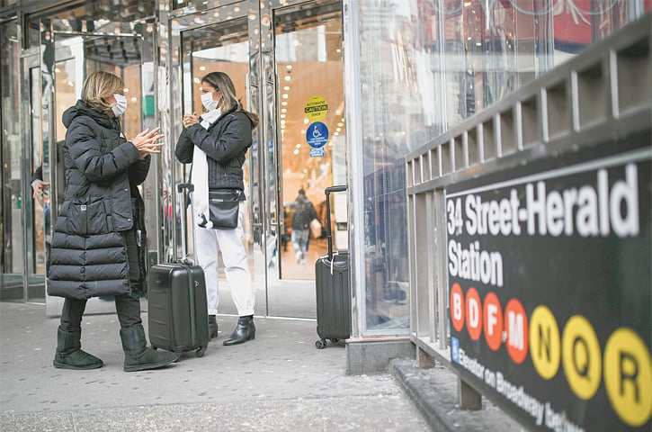 NEW YORK: Shoppers wearing masks sanitise their hands at the Herald Square on Thursday. New York City's mayor Bill de Blasio said he would announce restrictions on gatherings to halt the spread of coronavirus in the coming days.—AP