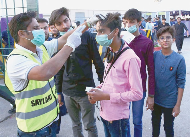 KARACHI: A health worker takes the body temperature of cricket lovers who came to watch the Pakistan Super League match between Karachi Kings and Lahore Qalandars on Thursday.—Agencies