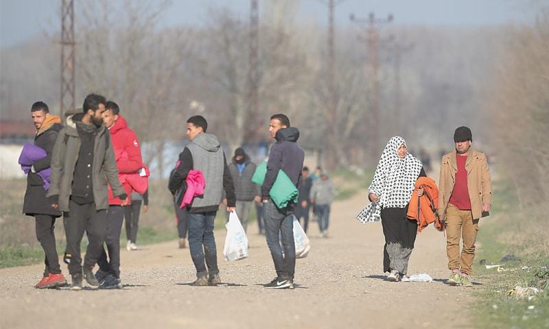 EDIRNE (Turkey): Migrants walk near the Turkish-Greek border in Pazarkule on Thursday. —AP