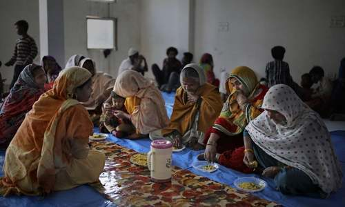 In this February 2020 file photo, Muslim women, who were rescued after their homes were attacked by a marauding Hindu mob, sob while eating a meal inside a hall which doubles as a shelter at Al-Hind hospital in Old Mustafabad neighbourhood of New Delhi, India. — AP/File