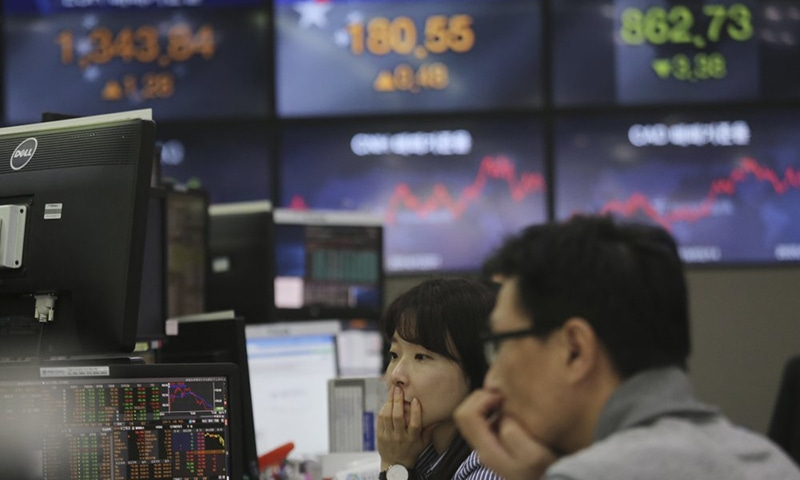 Currency traders watch monitors at the foreign exchange dealing room of the KEB Hana Bank headquarters in Seoul, South Korea on Friday. Shares plunged in Asia on Friday, with Japan's benchmark sinking as much as 10% after Wall Street suffered its biggest drop since the Black Monday crash of 1987. — AP