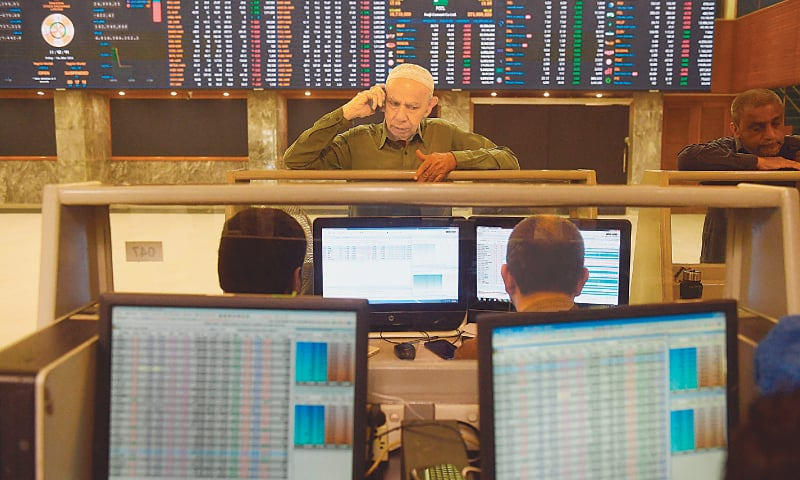 KARACHI: Stockbrokers monitoring share prices at the Pakistan Stock Exchange on Friday.—AFP