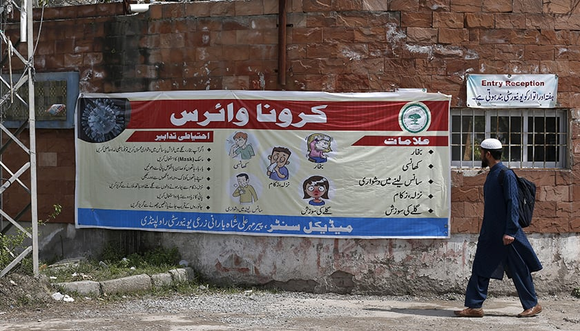 A student takes a look at a banner regarding the symptoms and precautions for the coronavirus at an entrance of a university in Rawalpindi on March 14. — AP