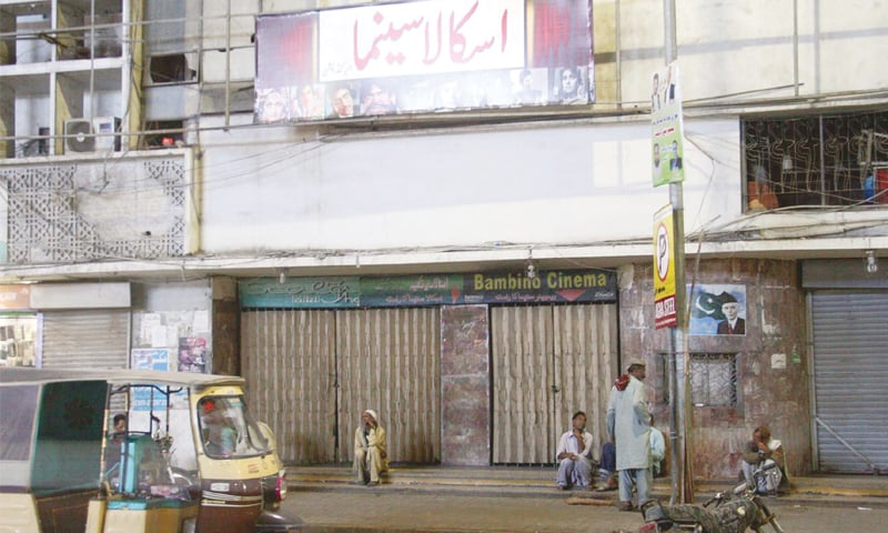 People pictured outside two closed cinema houses in Karachi and in Hyderabad