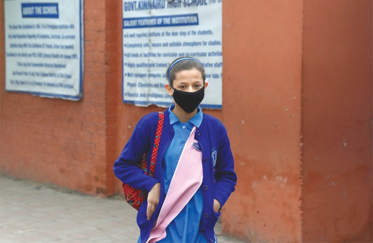 A student wearing mask in Lahore walks back to home on Saturday as her school is closed to prevent the spread of coronavirus.