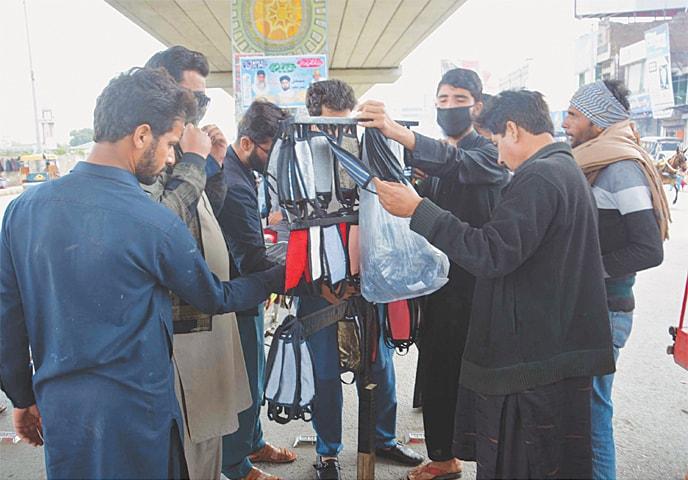 In Gujranwala, people buy face masks.