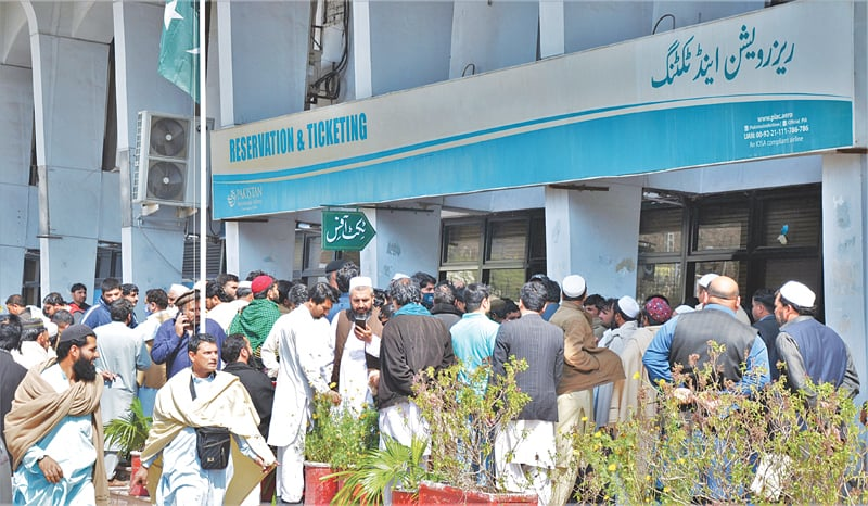Expatriates gather on the premises of PIA ticketing office in Peshawar to get rescheduled their flights to various Gulf countries from Bacha Khan airport after international flights were cancelled due to virus outbreak.