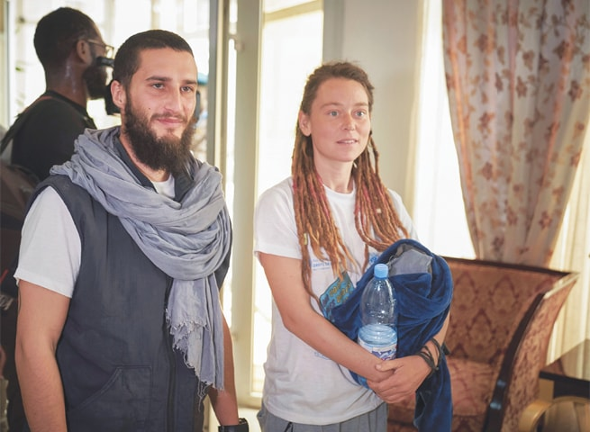 Italian Luca Tacchetto (left) and Canadian Edith Blais (right) are greeted by officials as they arrive at the airport in Bamako on Saturday after their release by UN peacekeepers.—AFP