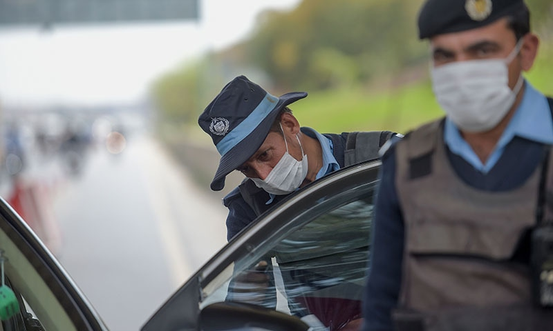 Policemen wearing facemasks as a preventive measure against the spread of the COVID-19 coronavirus, search a car at the capital entry checkpoint in Islamabad on March 14. — AFP