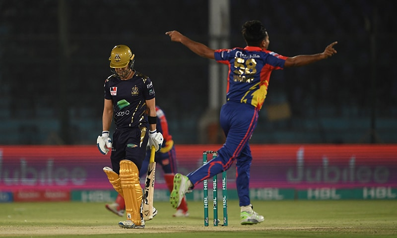Karachi King's Waqas Maqsood (R) celebrates the wicket of Quetta Gladiators Ahmad Shahzad(L)walks back to the pavilion during the PSL T20 cricket match between Karachi King's and Quetta Gladiators at the National Stadium in Karachi on March 15, 2020. — AFP