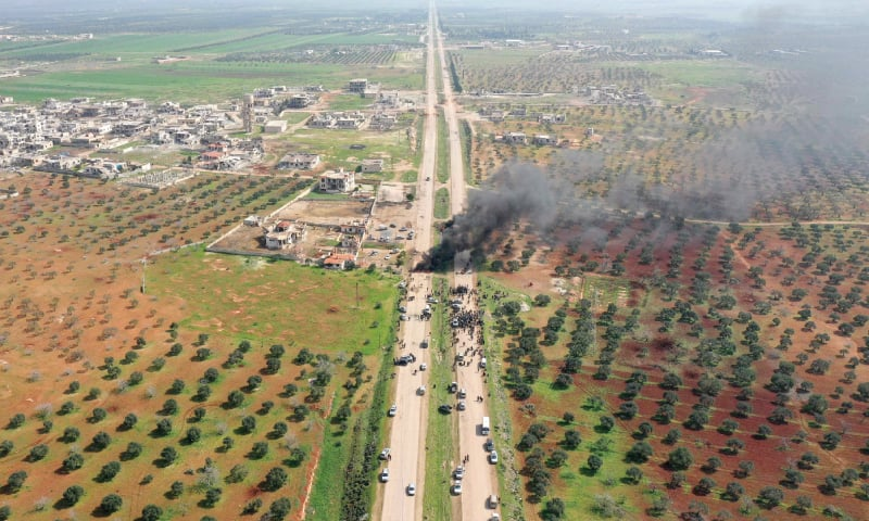 ALEPPO: Syrians try to block traffic on a highway, which links the northern provinces of Aleppo and Latakia, before the arrival of joint Turkish and Russian military patrols in a village near Aleppo on Sunday.—AFP
