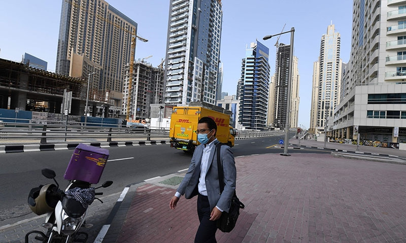 A man, wearing a protective mask, walks down the street in Dubai on March 16, 2020. - No shisha pipe sessions, deserted streets, mosques and shopping malls, drones in the sky broadcasting public health warnings — the new coronavirus has turned life upside down in Gulf societies. — AFP