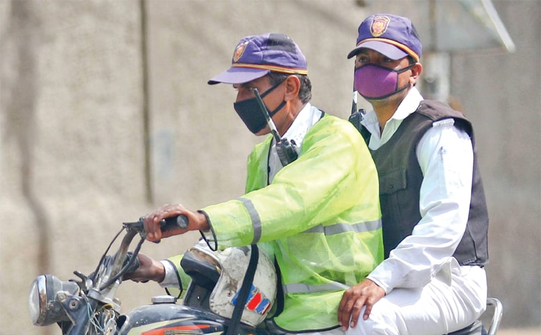 TWO traffic policemen ride a motorcycle wearing face masks on Monday.—INP