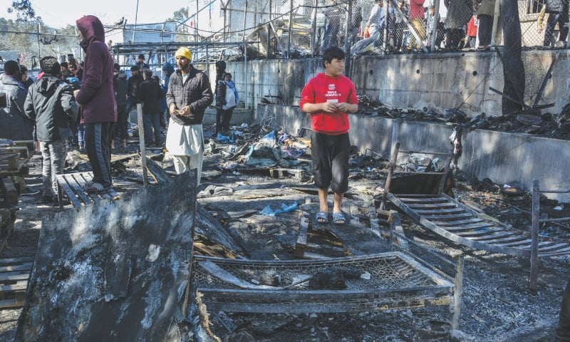 LESBOS: Migrants stand on a burned container home in a refugee camp on the Greek island of Lesbos on Monday.—AP