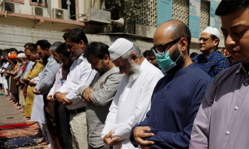 A man wears a protective mask as a preventive measure amid coronavirus fears, as he attends Friday prayers with others in Karachi, Pakistan on March 13. — Reuters