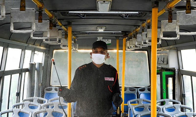 A worker sprays disinfectant to sanitize a public bus as a preventive measure against COVID-19 in Kathmandu on March 18. — AFP