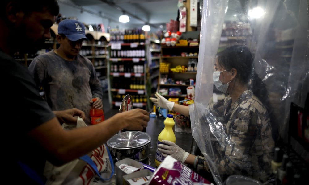 A supermarket cashier waits for costumers behind a makeshift plastic curtain as a precaution against the spread of the new coronavirus, in Buenos Aires, Argentina on March 16, 2020. — AP