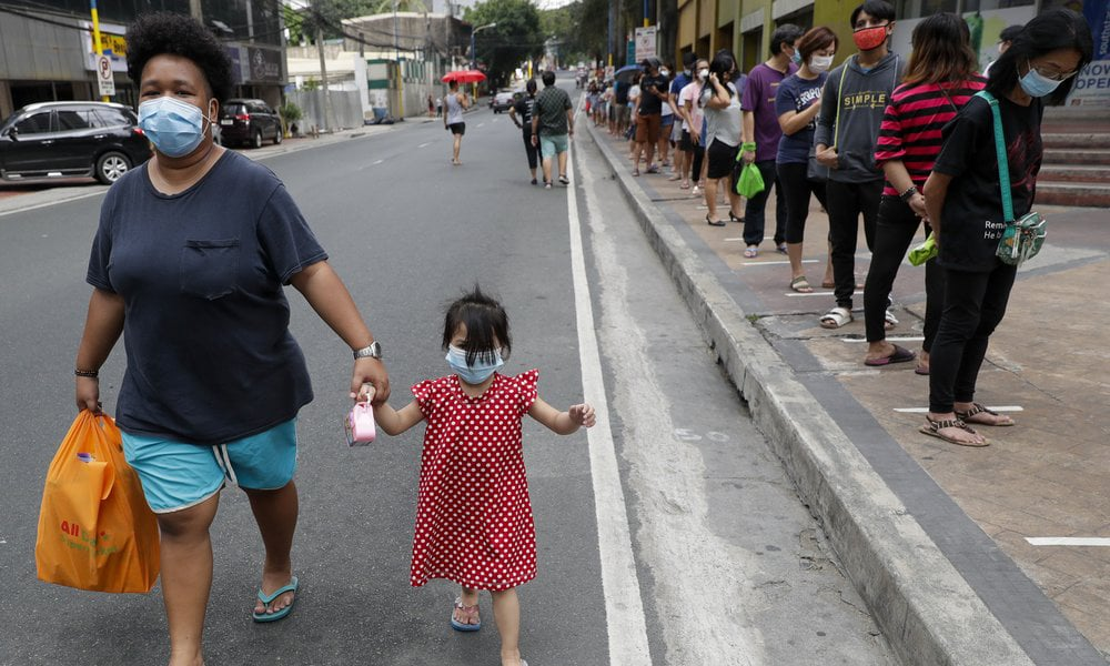 Residents line outside a supermarket in Manila, Philippines, while the government implements a localized quarantine as a precautionary measure against the spread of the new coronavirus on March 17, 2020. — AP
