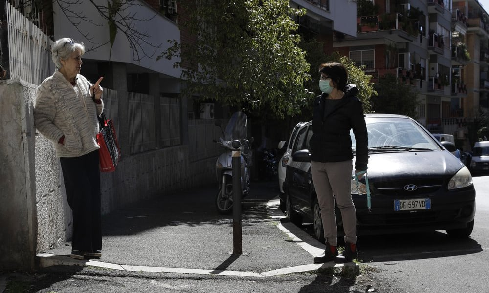 Enza Garzia, 79, left, talks at a distance with Paola Albano, in central Rome on March 11, 2020. — AP