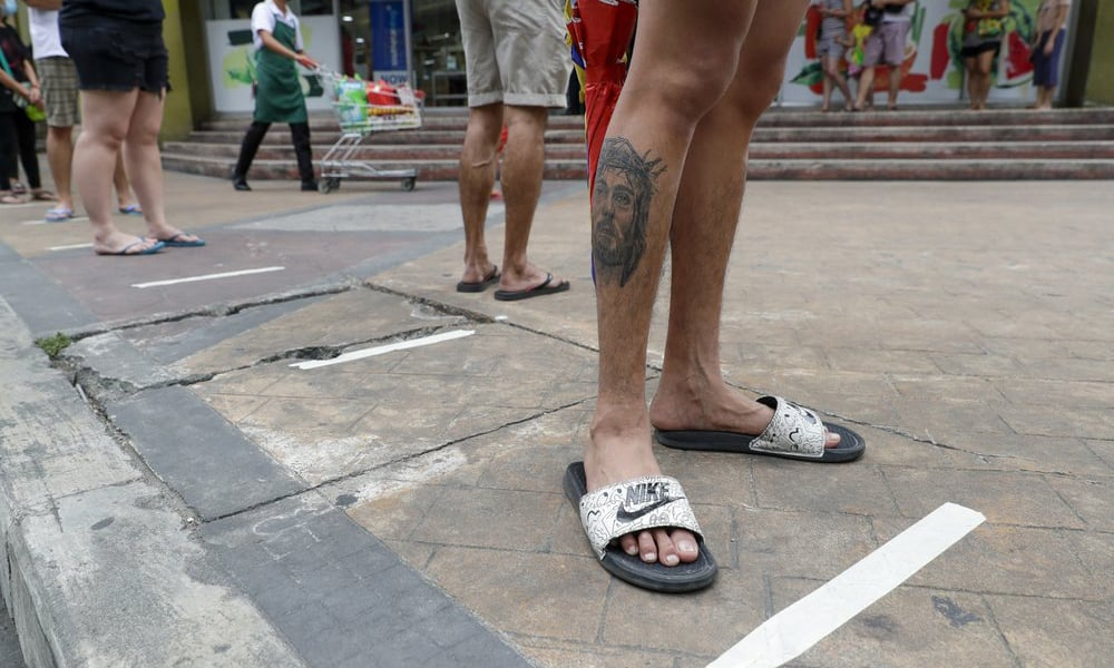 Residents step on measured tape placed outside a supermarket to practice social distancing as a precautionary measure against the spread of the coronavirus in Metro Manila, Philippines on March 17, 2020. — AP