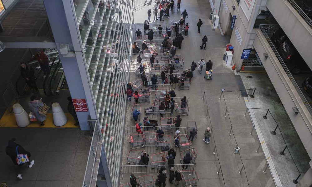Customers make a line with the shopping carts at a New York retail store on March 16, 2020. — AP