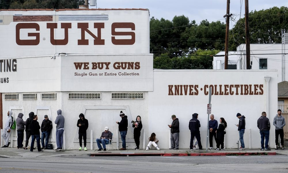 People wait in a line to enter a gun store in Culver City, Calif on March 15, 2020. — AP