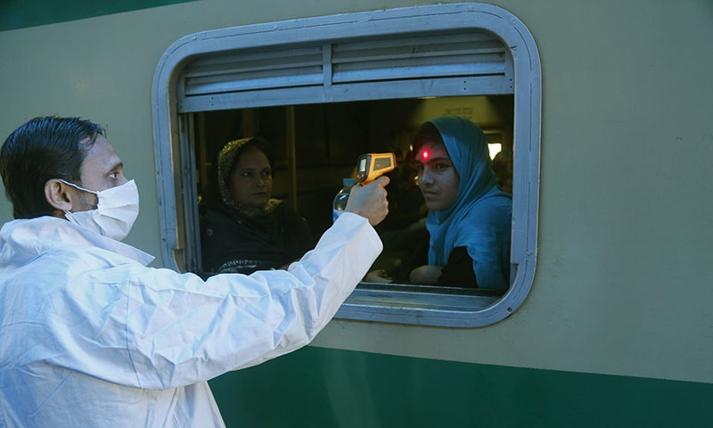 A Pakistani volunteer checks the body temperature of a passenger to help detect coronavirus, at a railway station in Lahore, Pakistan on Wednesday, March 18, 2020. — AFP