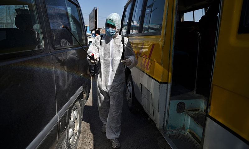 A volunteer wearing a hazmat suit and a mask sprays disinfectant on vehicles during a preventive campaign against the spread of the COVID-19 coronavirus in Kabul on March 18, 2020. — AFP