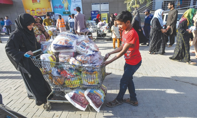 An overloaded shopping cart is being pushed and pulled as other such carts follow right behind in the parking lot of a super store. —Fahim Siddiqi / White Star