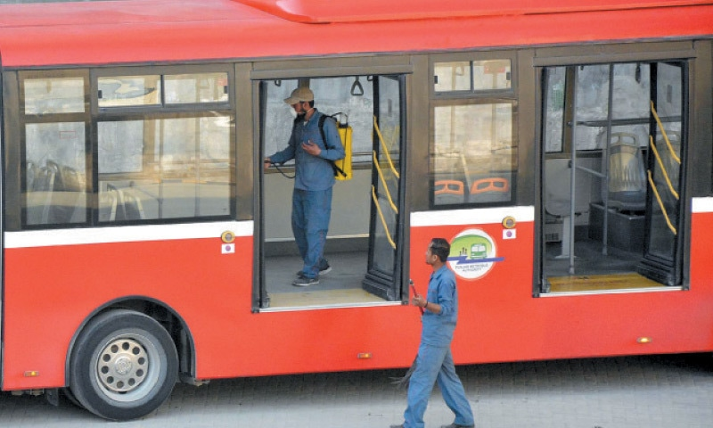 An employee of the metro service sprays a bus at the Secretariat station as a prevention against coronavirus on Wednesday. — Online