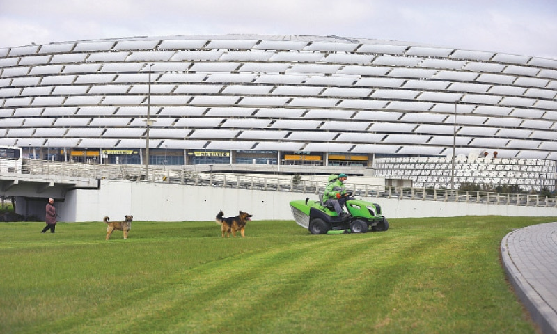BAKU: A worker rides a tractor as he mows a lawn on Wednesday in front of the Olympic Stadium, which was due to host four Euro 2020 matches, including a quarter-final.—AP