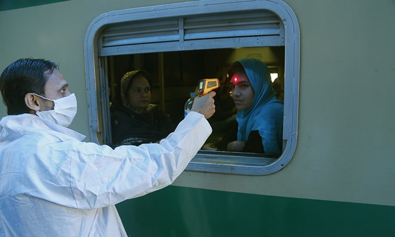 A Pakistani volunteer checks the body temperature of a passenger to help detect coronavirus, at a railway station in Lahore on March 18. — AP