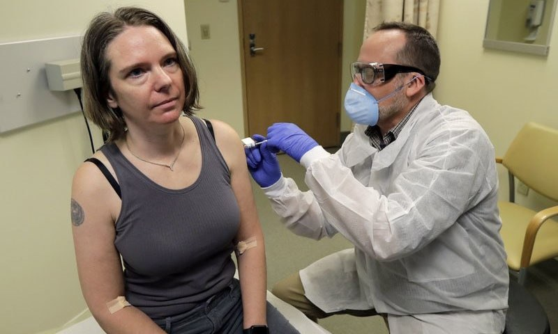 A pharmacist gives Jennifer Haller the first shot in the first-stage safety study clinical trial of a potential vaccine for COVID-19, the disease caused by the new coronavirus on March 16, 2020. — AP