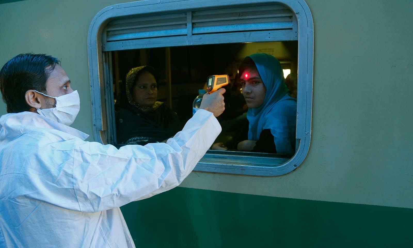 رضاکار ٹرین میں مسافروں کی اسکریننگ کر رہے ہیں — فوٹو: اے پی