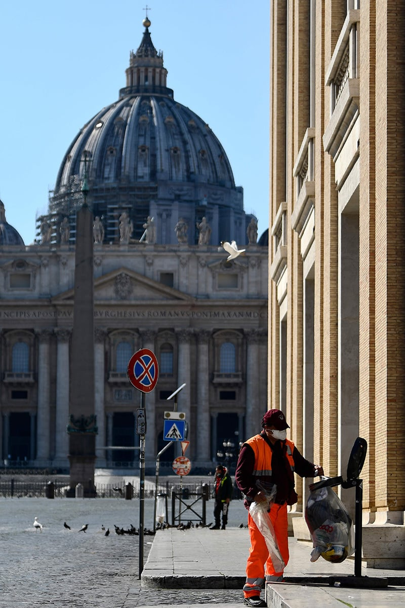 A garbage man empties a public trash on March 19, 2020 in Rome, with the Vatican's St. Peter's basilica in background, during the lockdown due to the new coronavirus pandemic.  — AFP