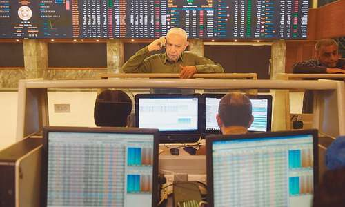 Stockbrokers monitoring share prices at the Pakistan Stock Exchange in Karachi on Friday.—AFP