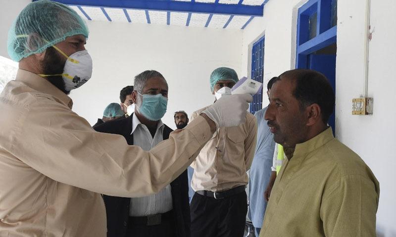 ایران سے آنے والے شخص کا بخار چیک کیا جا رہا ہے—تصویر بشکریہ اے ایف پی