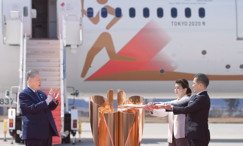 HIGASHIMATUSHIMA: Three-time Olympic gold medallists Tadahiro Nomura (R) and Saori Yoshida light the torch as Tokyo 2020 Olympics chief Yoshiro Mori looks on during the Olympic Flame Arrival Ceremony at the Matsushima Base on Friday.—AP