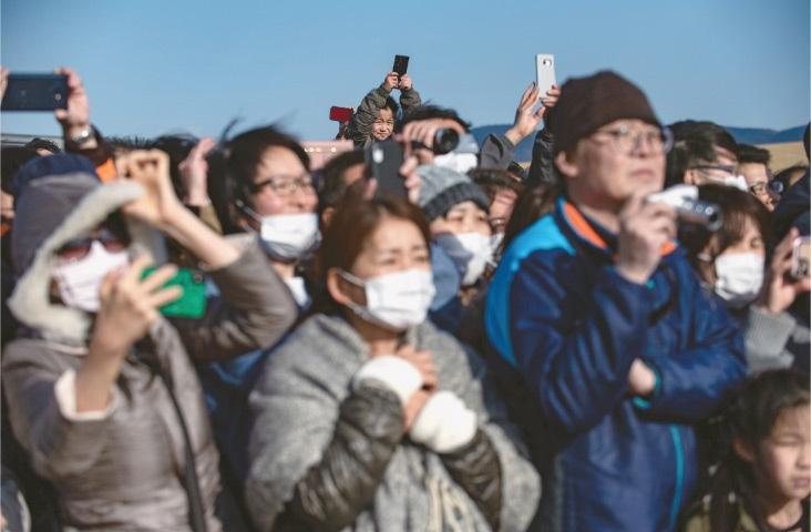 ISHINOMAKI: Spectators attend the unveiling of the Tokyo 2020 Olympic flame at Ishinomaki Minamihama Tsunami Recovery Memorial Park on Friday.—AFP