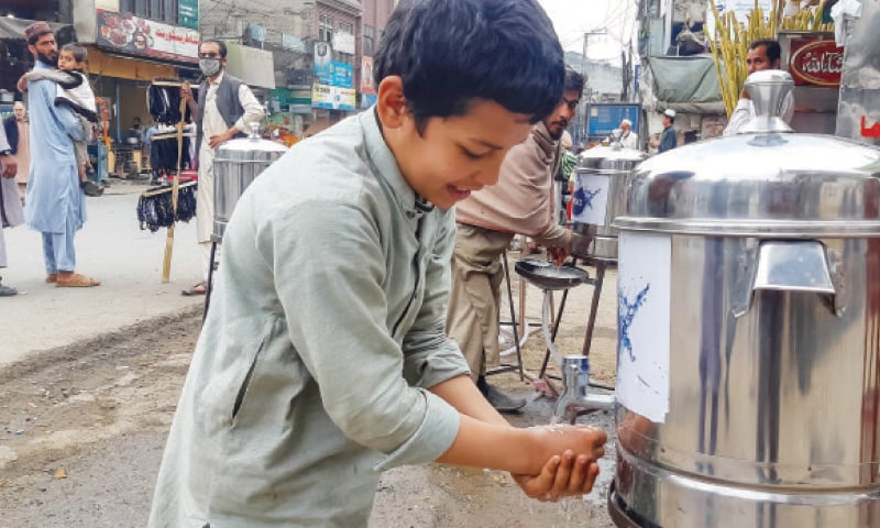A boy washes hands at a facility installed by WSSC in Mingora. — Dawn