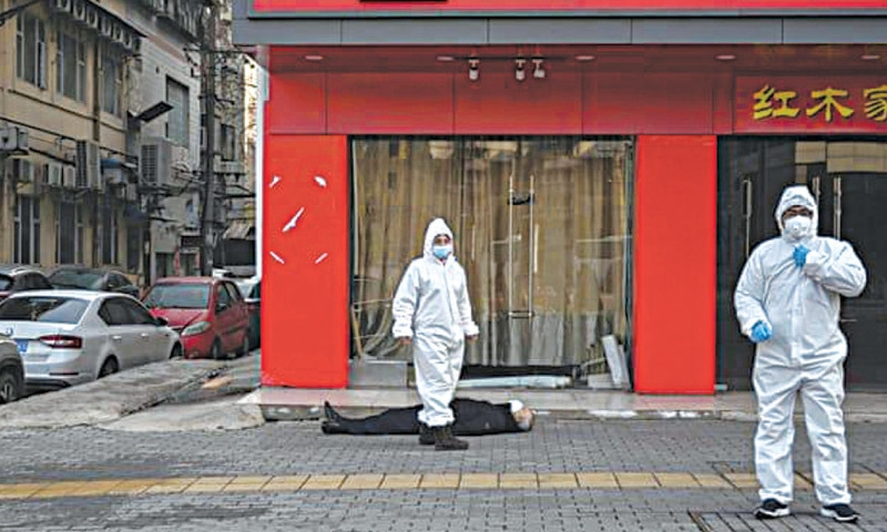 Emegency staff in protective suits check the body of a man lying in an empty street in Wuhan | AFP