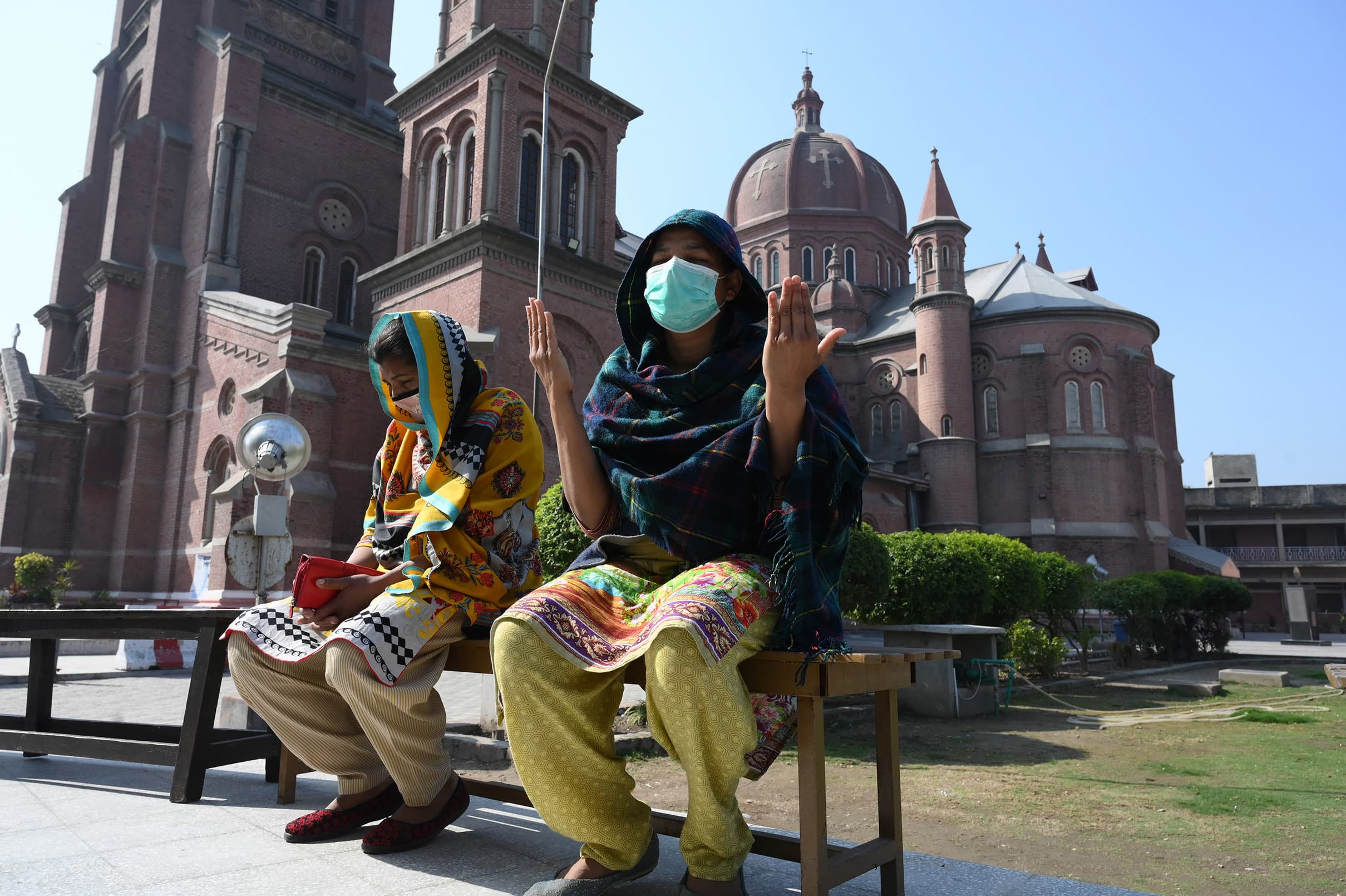 Women wearing masks pray outside Lahore's Sacred Heart Cathedral, one of the churches that has been closed down to discourage large congregations | M Arif, White Star