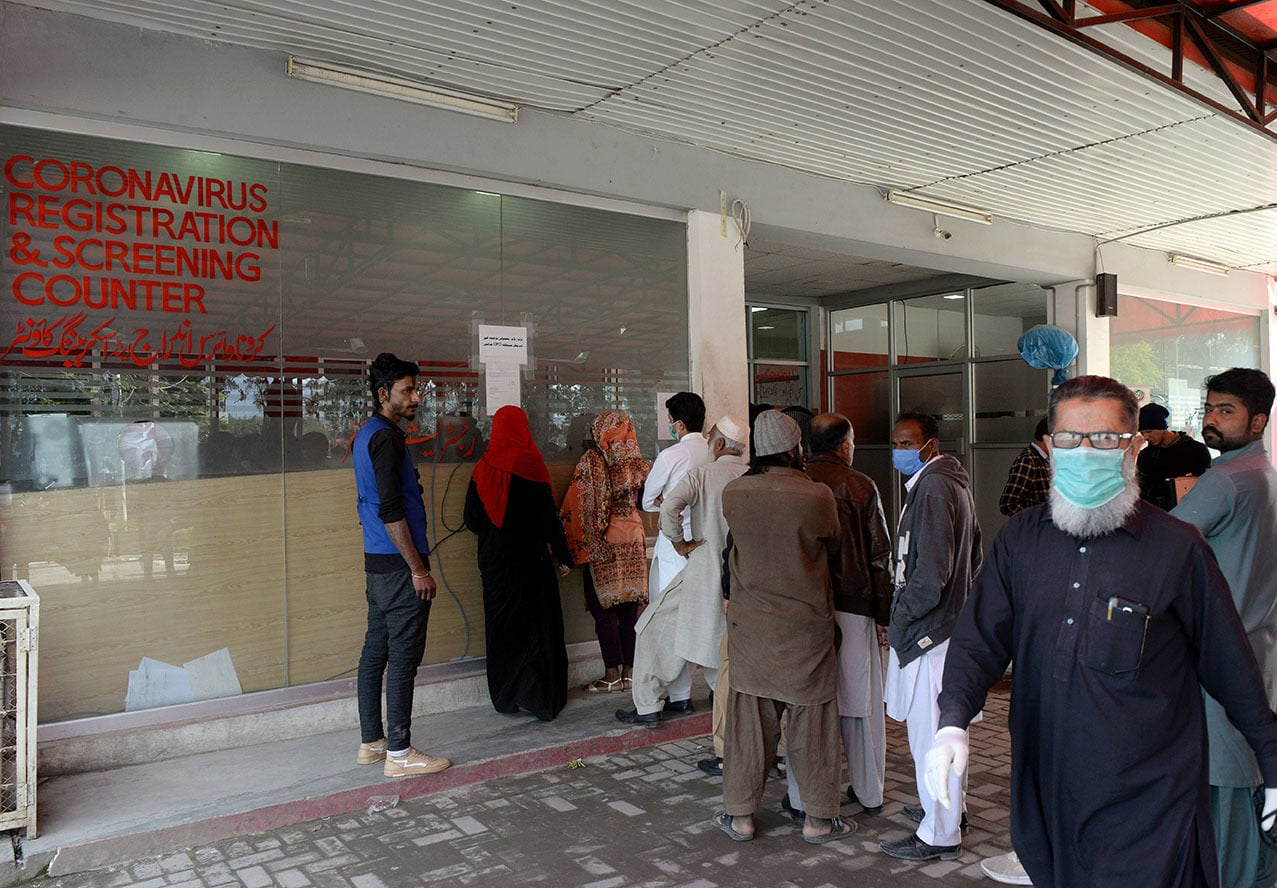 People wait behind a coronavirus registration and screening counter at Pakistan Institute of Medical Sciences hospital in Islamabad | Mohammad Asim, White Star