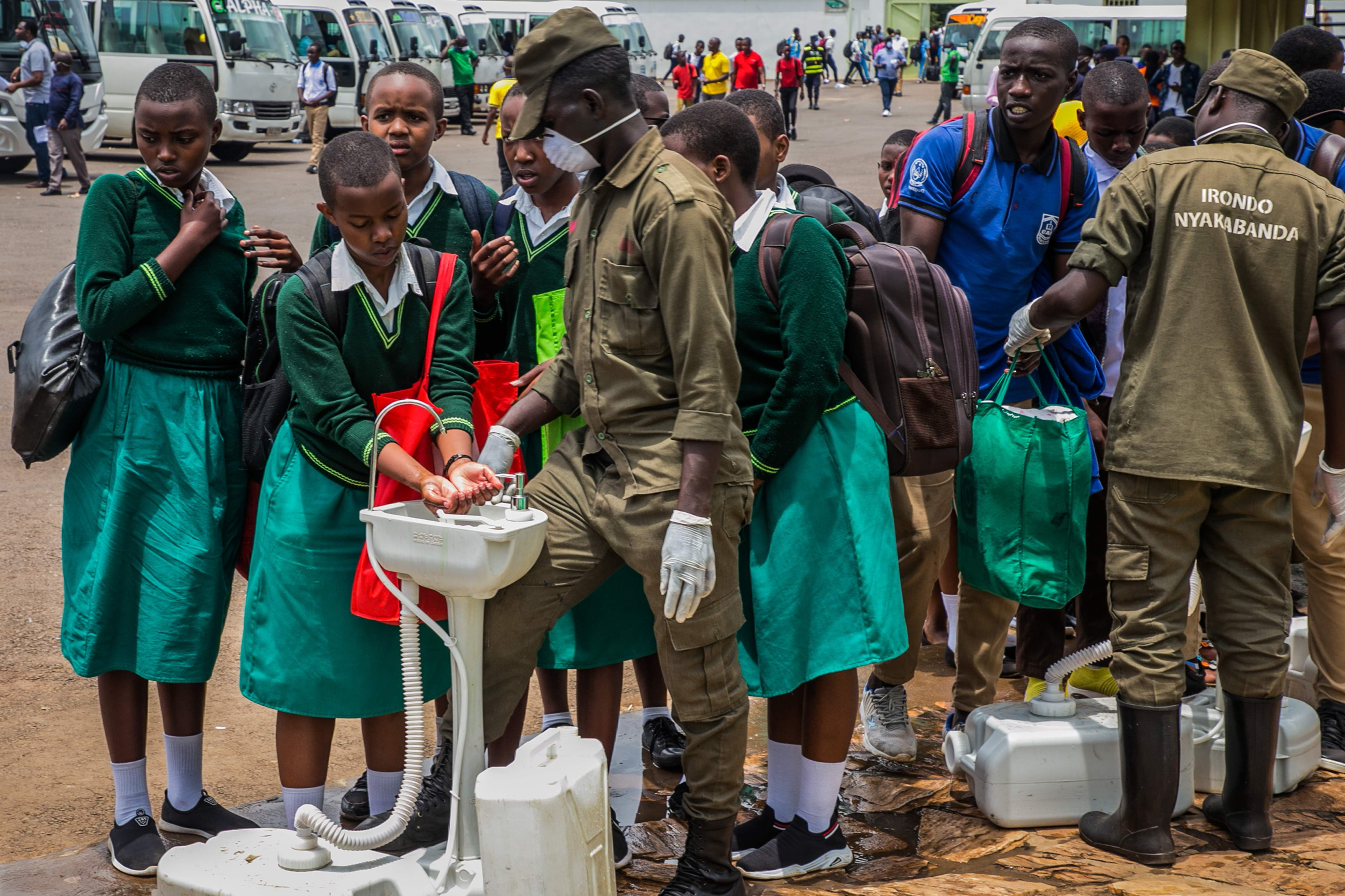 Rwandan students wash their hands at temporary hand washing points before they are sent back home from boarding schools | AFP