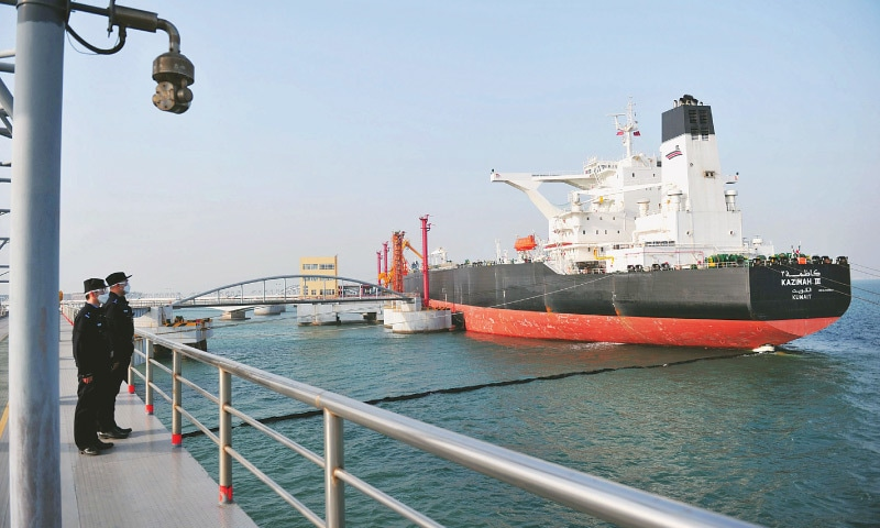 Qingdao (China): Police officers keeping watch as a Kuwaiti oil tanker unloads crude oil at the port in eastern Shandong province.—AFP